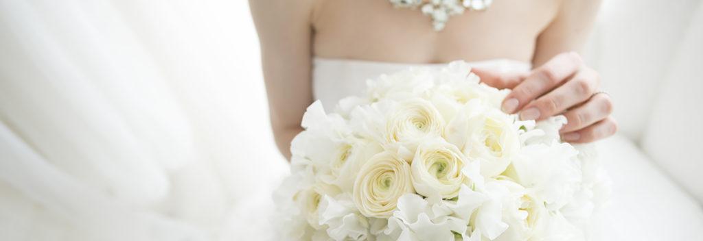 白いブーケを持ったウェディングドレス姿の花嫁の画像。